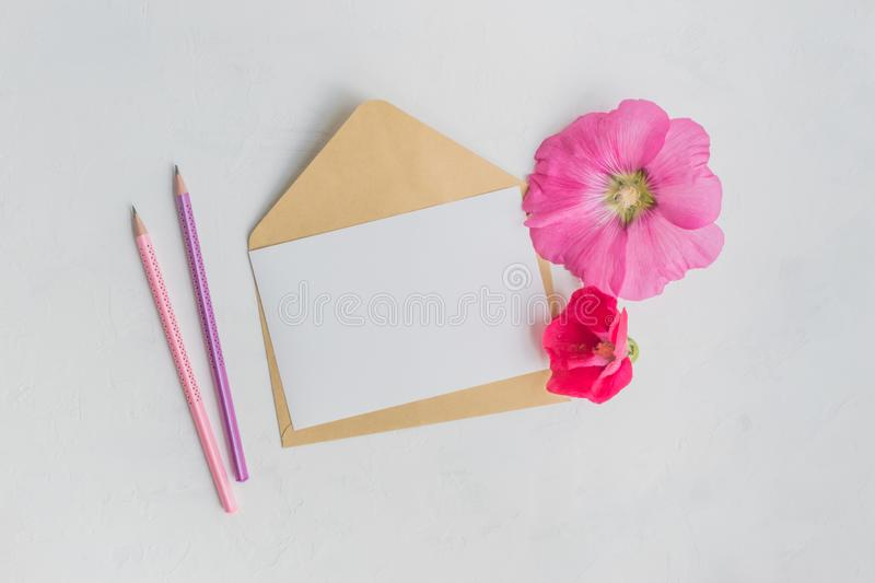 Mockup white greeting card and envelope with pink flowers. On a  light background stock photos