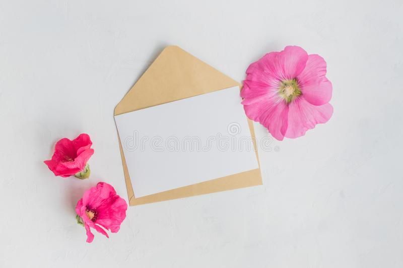 Mockup white greeting card and envelope with pink flowers. On a  light background stock image