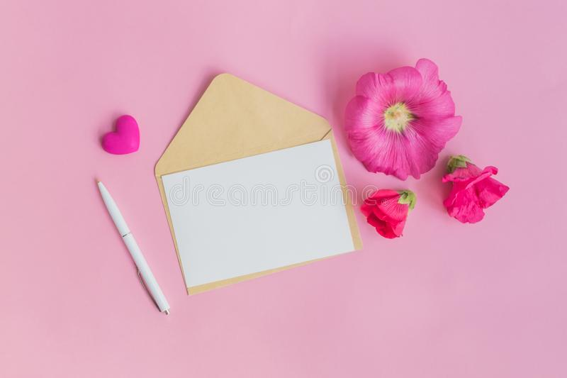 Mockup white greeting card and envelope with pink flowers. On a pink background royalty free stock image