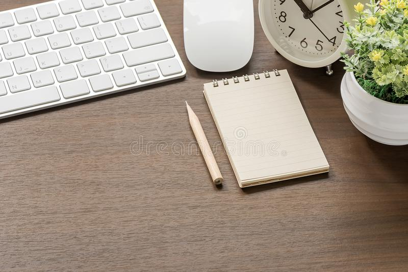 Mockup of white keyboard, mouse, blank notebook, pencil,alarm cl. Ock and houseplant on wooden table with copy space royalty free stock photography