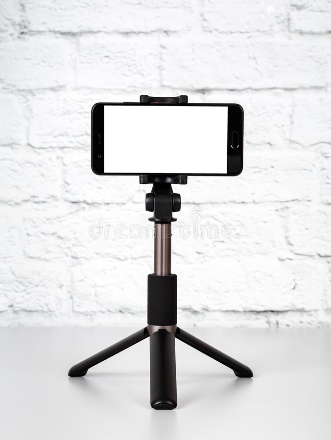Free Mockup With Smartphone On A Tripod With Empty Screen Royalty Free Stock Images - 127299479