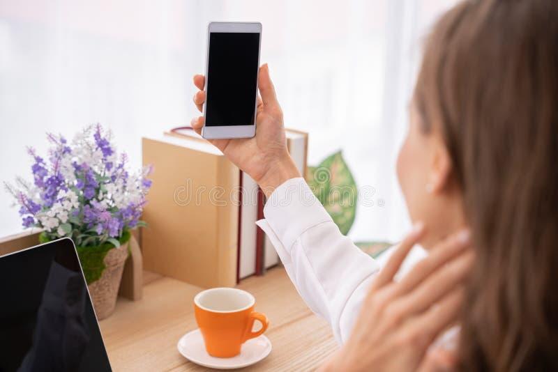 Mockup wizerunek kobiet ręki trzyma białego telefon komórkowego z pustym czerń ekranem w jaskrawym łóżkowym pokoju zdjęcia royalty free