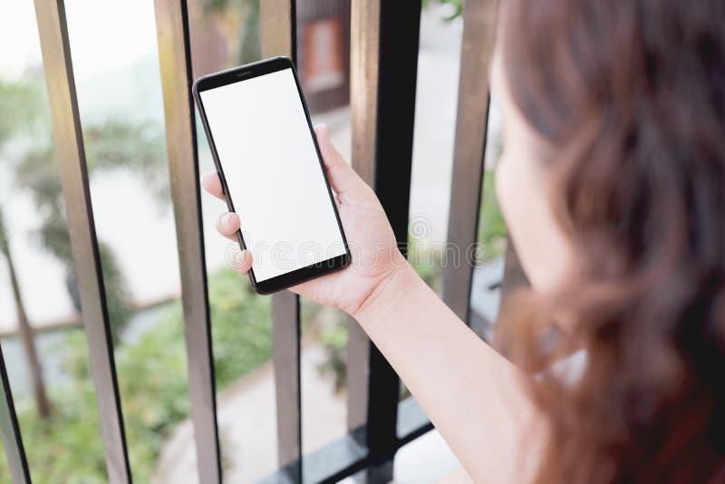 Mockup wizerunek kobieta używa mądrze telefon z pustym bielu ekranem i ogrodową naturą na parteru tle w domu zdjęcie royalty free