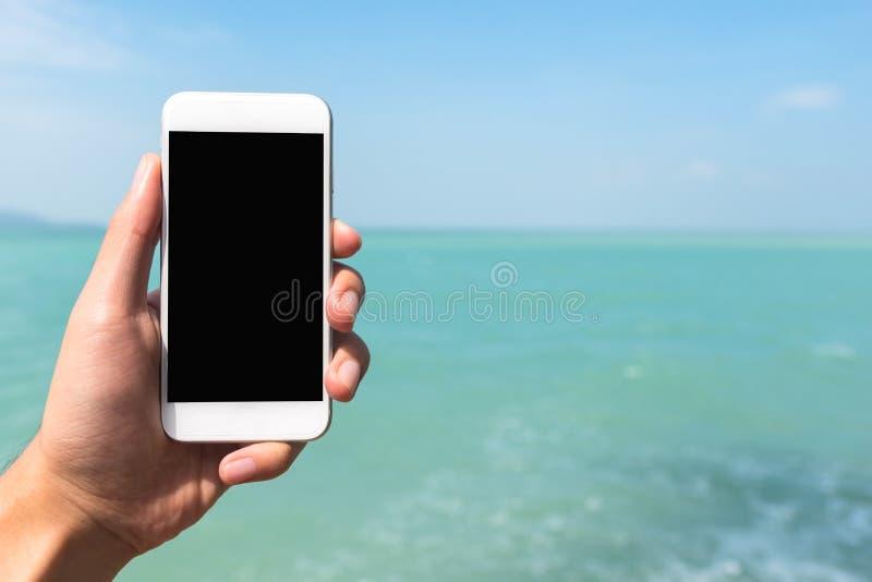 Mockup wizerunek ręka trzyma białego telefon komórkowego z pustym czarnym desktop ekranem przed morzem i pokazuje obrazy royalty free