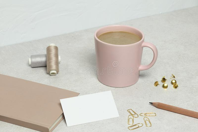Mockup wizytówka, książka, ołówek, papierowe klamerki, szpilki i nici, filiżanka kawy na granitowej teksturze fotografia stock