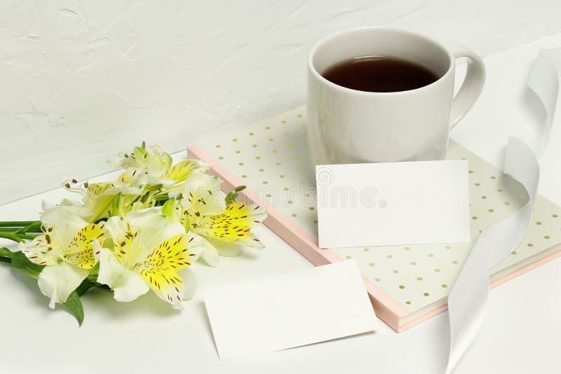 Mockup wizytówki na białym tle z pięknymi kwiatami, notatkami, faborkiem i filiżanka kawy, fotografia stock