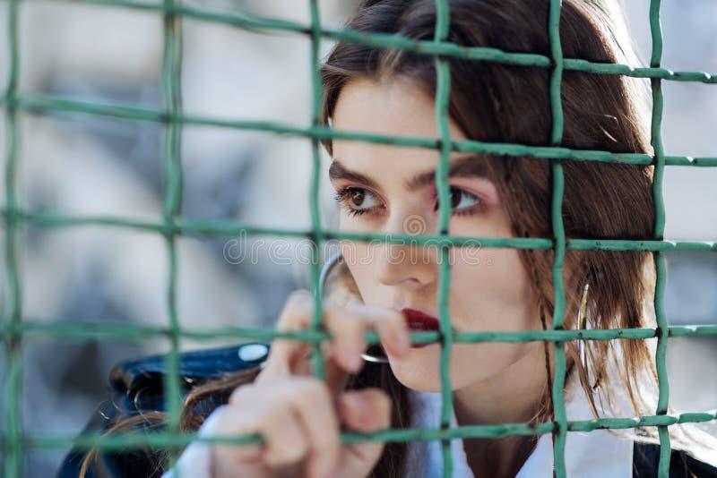 Modèle à la mode sérieux de photo posant près de la barrière au stade photographie stock