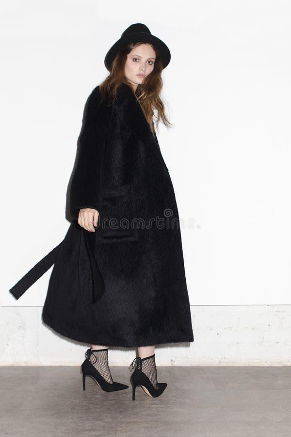 Modèle élégant dans le long manteau noir image libre de droits
