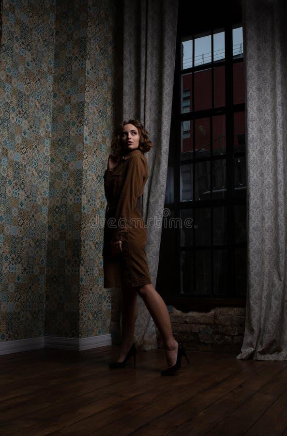 Modèle élégant de brune avec les cheveux bouclés portant la robe brune posant près des rideaux en cru image libre de droits