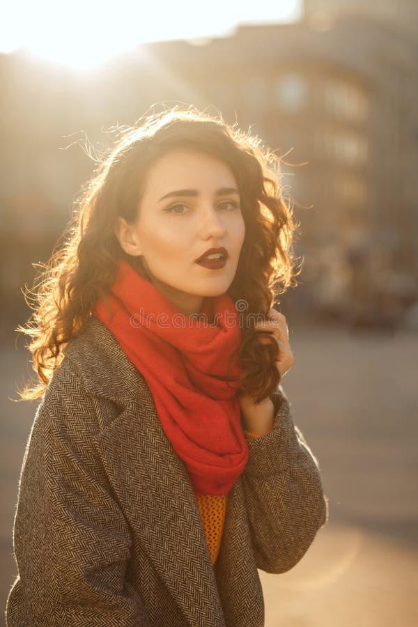 Modèle élégant de brune avec les cheveux luxuriants posant dans le contre-jour égalisant mou à l'avenue photos libres de droits