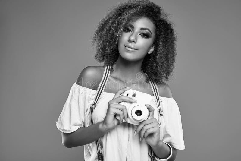 Modèle élégant de femme de couleur avec les cheveux bouclés et l'appareil-photo photo libre de droits