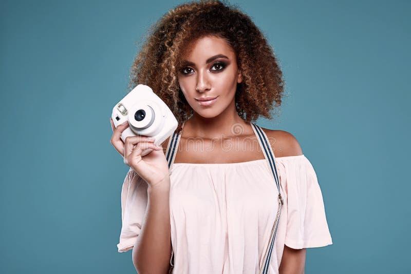 Modèle élégant de femme de couleur avec les cheveux bouclés et l'appareil-photo image libre de droits