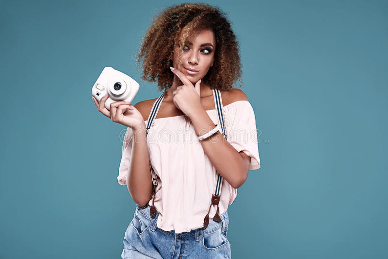 Modèle élégant de femme de couleur avec les cheveux bouclés et l'appareil-photo photo stock