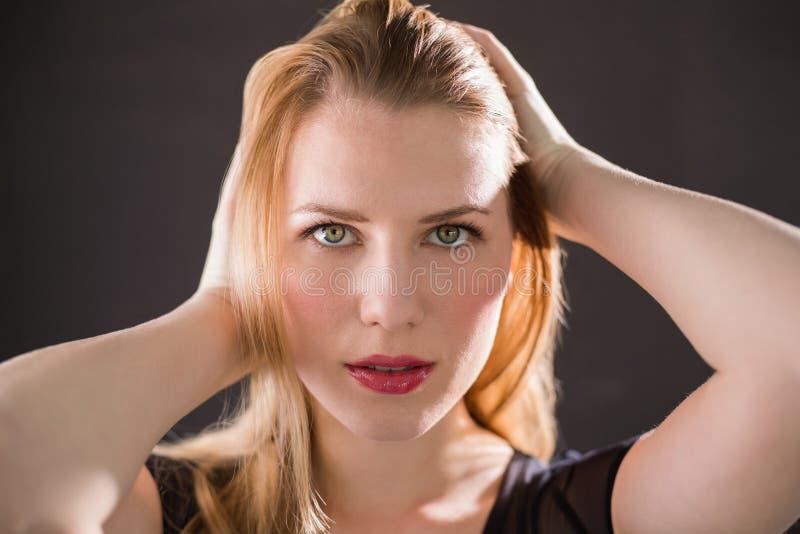 Modèle assez blond dans la robe noire posant des mains dans les cheveux photo stock