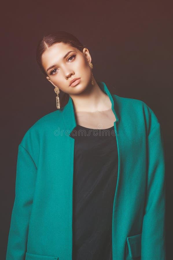 Modèle attrayant de jeune fille avec les cheveux foncés dans une veste verte et des bijoux à la mode sur un fond noir photos stock