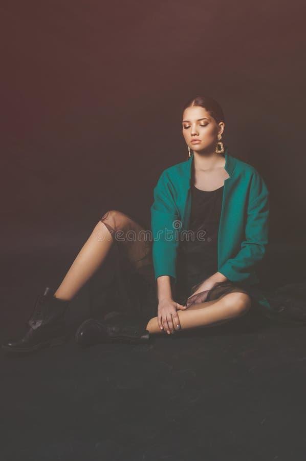 Modèle attrayant de jeune fille avec les cheveux foncés dans une veste verte et des bijoux à la mode sur un fond noir images stock