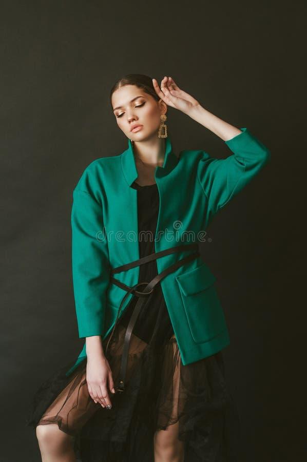 Modèle attrayant de jeune fille avec les cheveux foncés dans une veste verte et des bijoux à la mode sur un fond noir image libre de droits