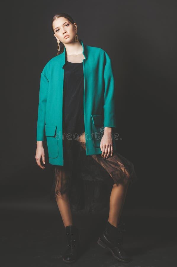 Modèle attrayant de jeune fille avec les cheveux foncés dans une veste verte et des bijoux à la mode sur un fond noir photos libres de droits