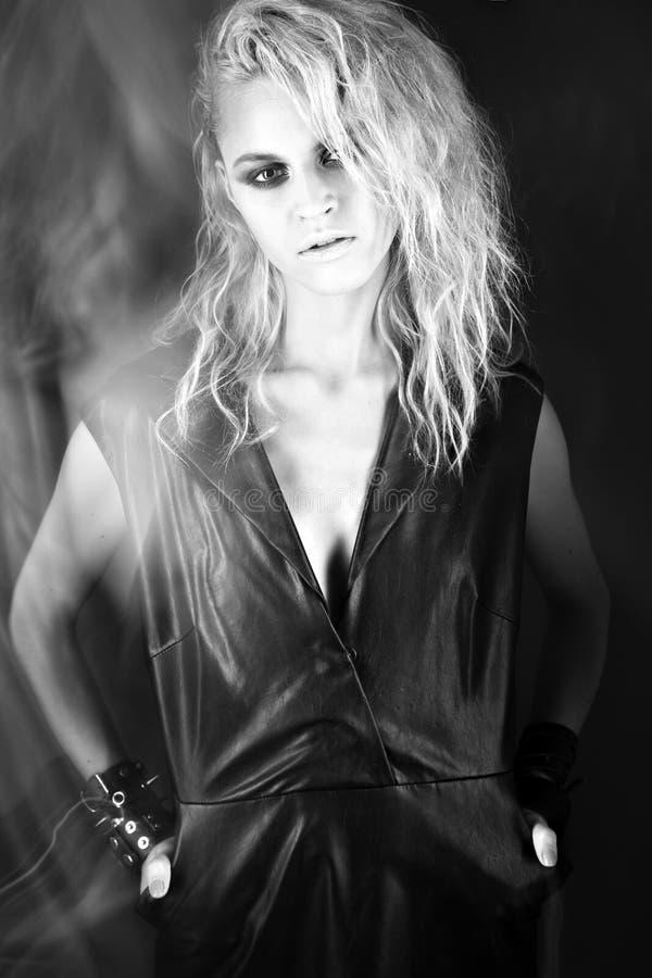 Modèle audacieux de fille dans la robe en cuir noire, style de roche, maquillage foncé, cheveux humides et bracelets sur ses bras photos libres de droits