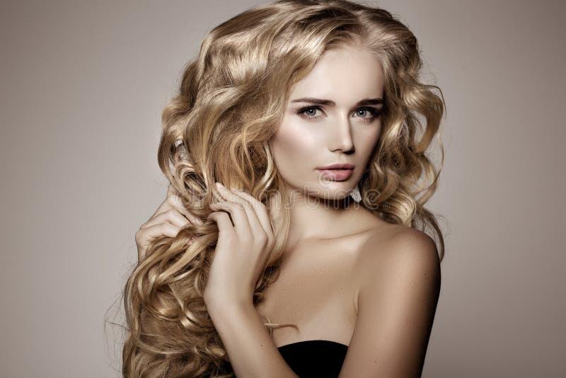 Modèle avec de longs cheveux blonds Coiffure de boucles de vagues Salon de coiffure photos stock
