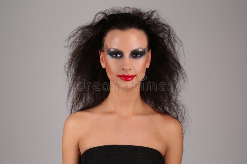 Modèle avec le maquillage et les cheveux sauvages Fin vers le haut Fond gris images stock