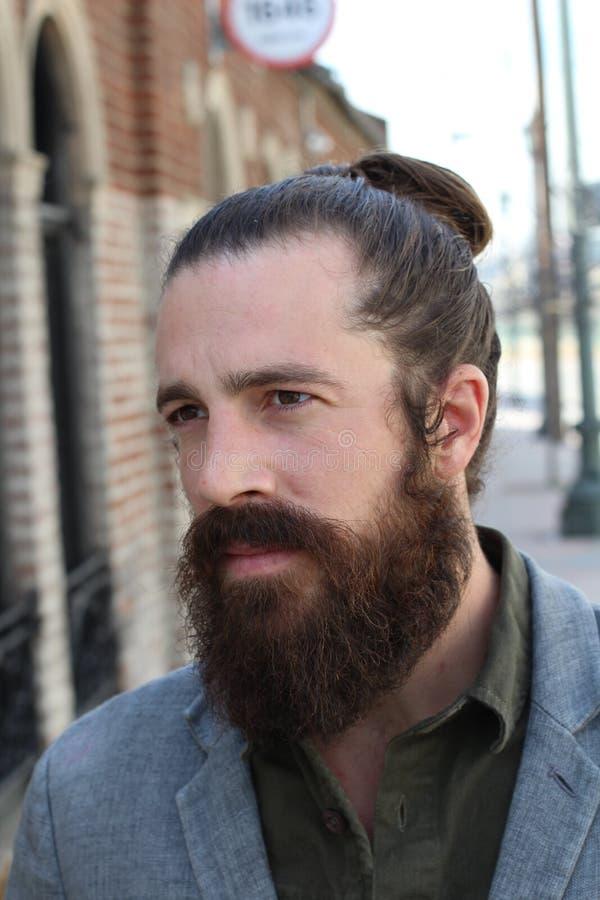 Modèle barbu de hippie avec la coiffure de petit pain de l'homme photo stock