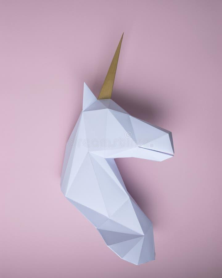 Modèle blanc du papercraft 3d de tête de licorne sur le fond rose Art Concept minimal photos libres de droits