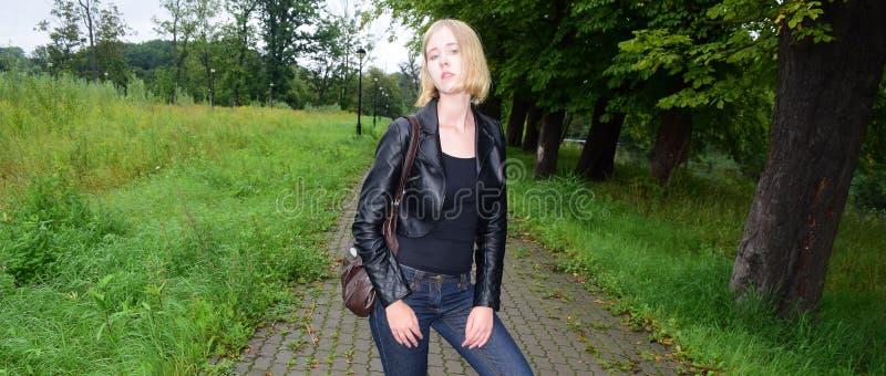Modèle blond de fille près d'une route en parc photographie stock libre de droits