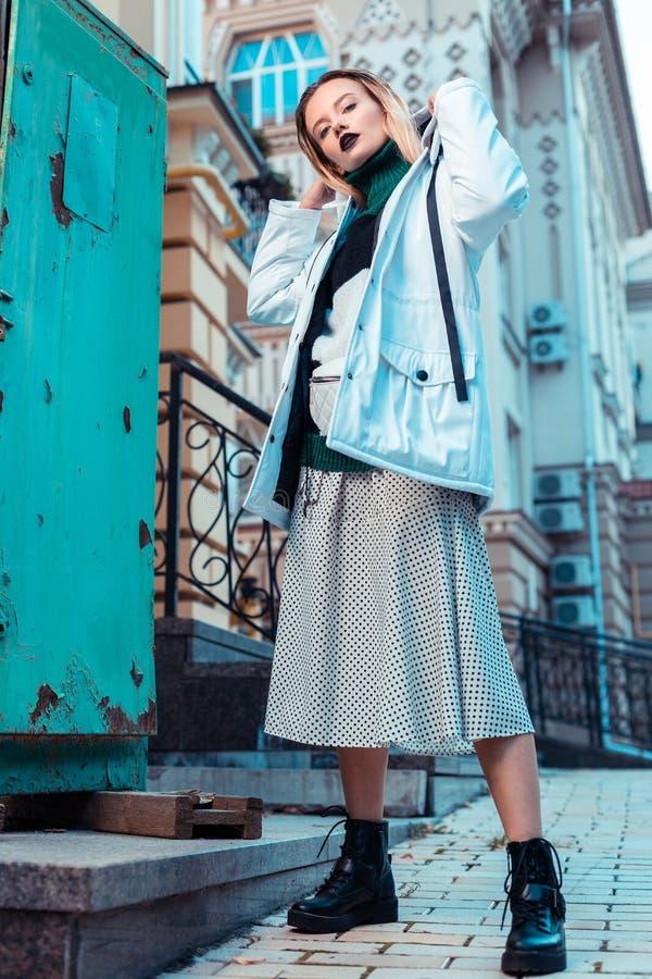 Modèle blond portant les bottes en cuir noires posant dans la rue image libre de droits