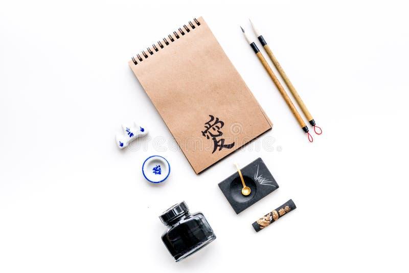 Modèle chinois ou japonais de calligraphie Hiéroglyphe dans le carnet de papier de métier et des accessoires d'inscription sur le photographie stock