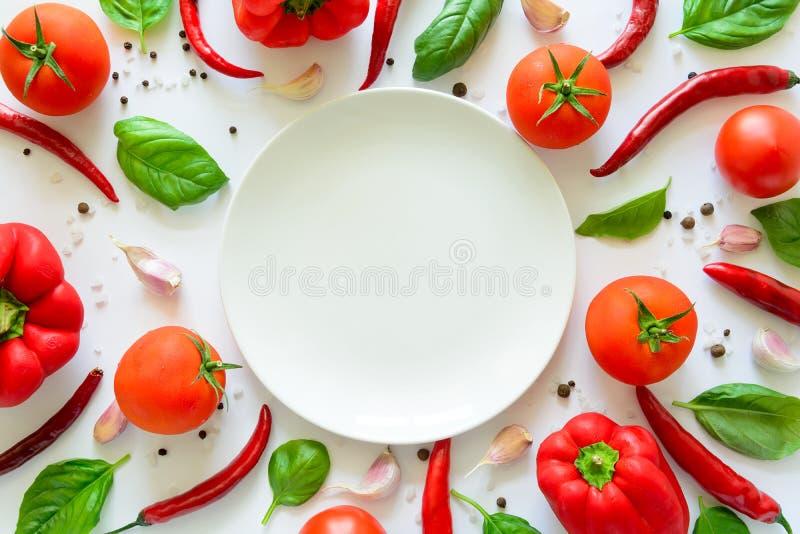 Modèle coloré d'ingrédients de pizza fait de tomates, poivre, piment, ail, basilic et plat vide sur le fond blanc photographie stock libre de droits