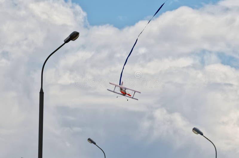 Modèle d'un avion de biplan dans le ciel urbain dans la perspective des nuages et des lanternes images libres de droits