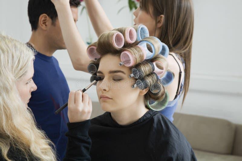 Modèle dans des bigoudis de cheveux faisant appliquer le maquillage image libre de droits