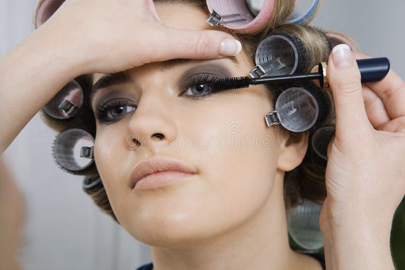 Modèle dans des bigoudis de cheveux faisant appliquer le maquillage photos stock