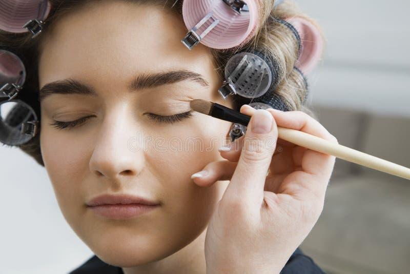 Modèle dans des bigoudis de cheveux faisant appliquer le maquillage image stock