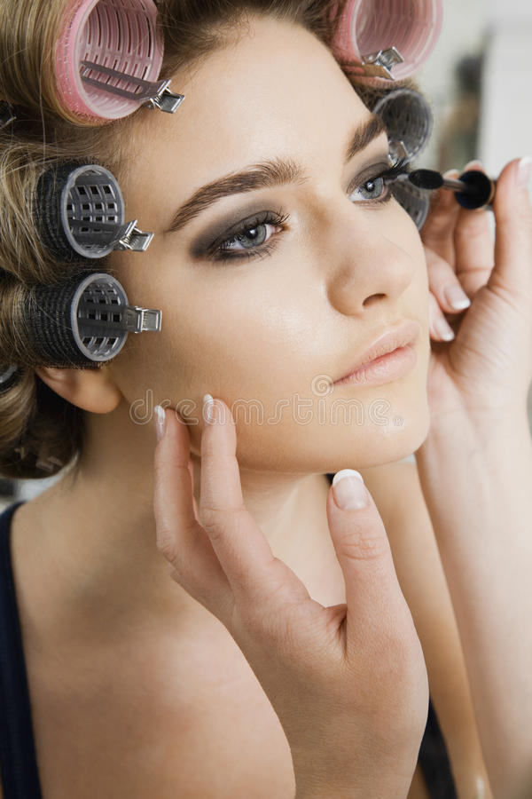 Modèle dans des bigoudis de cheveux faisant appliquer le maquillage photos libres de droits