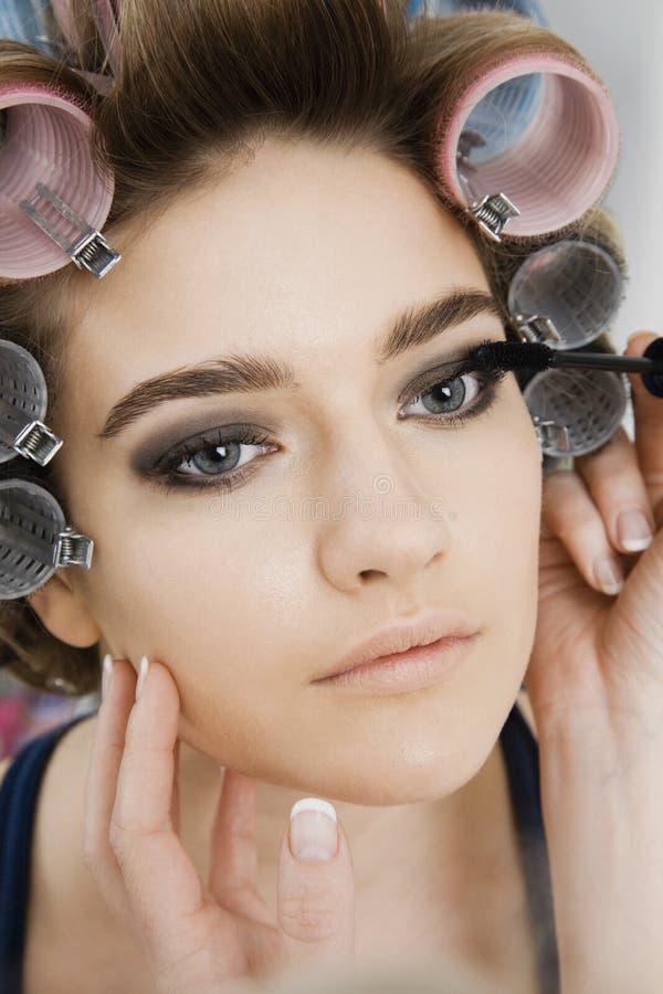 Modèle dans des bigoudis de cheveux faisant appliquer le maquillage photographie stock libre de droits
