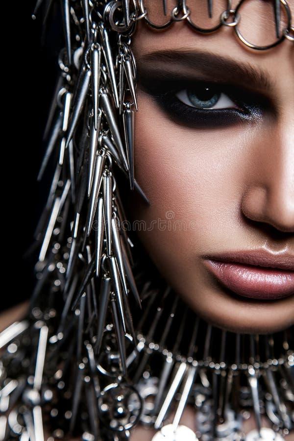 Modèle de beauté de haute couture avec le headwear métallique et le maquillage foncé et yeux bleus sur le fond noir photographie stock libre de droits
