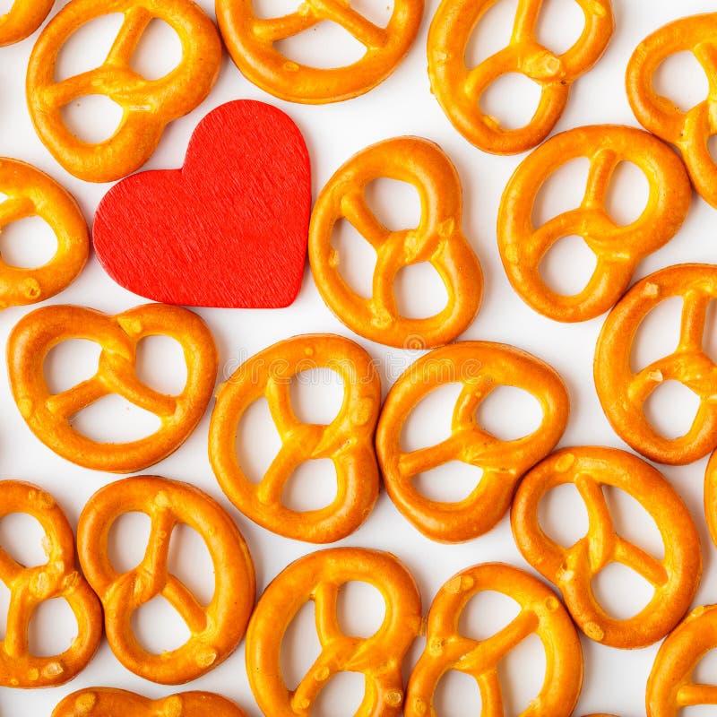Modèle de bretzels de fond de Saint-Valentin et coeur rouge. images stock