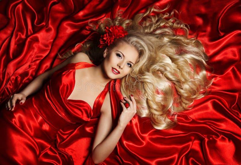 Modèle de cheveux, mensonge blond de femme de mode sur le tissu en soie rouge photographie stock