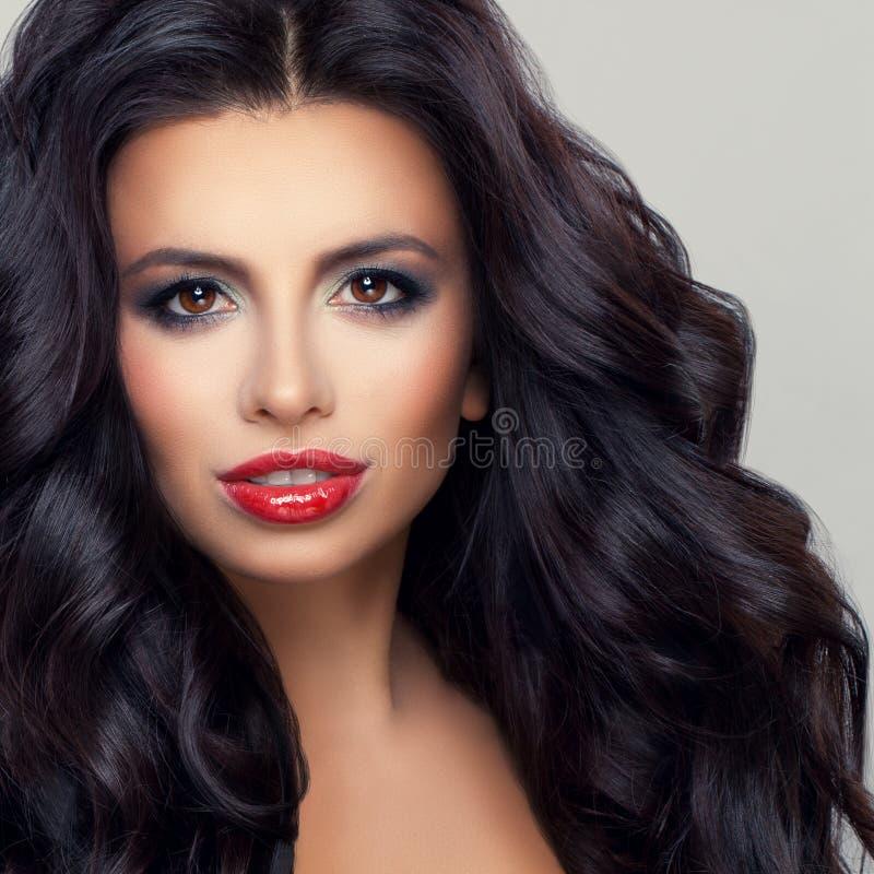 Modèle de femme de brune avec les cheveux bouclés sains et le maquillage photos libres de droits