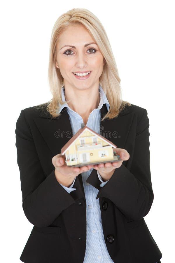 Modèle de fixation de femme d'affaires d'une maison photographie stock