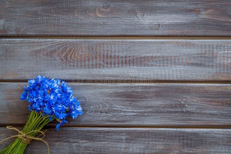 Modèle de fleurs d'été avec le bouquet des bleuets bleus sur la moquerie en bois de vue supérieure de fond  photos stock