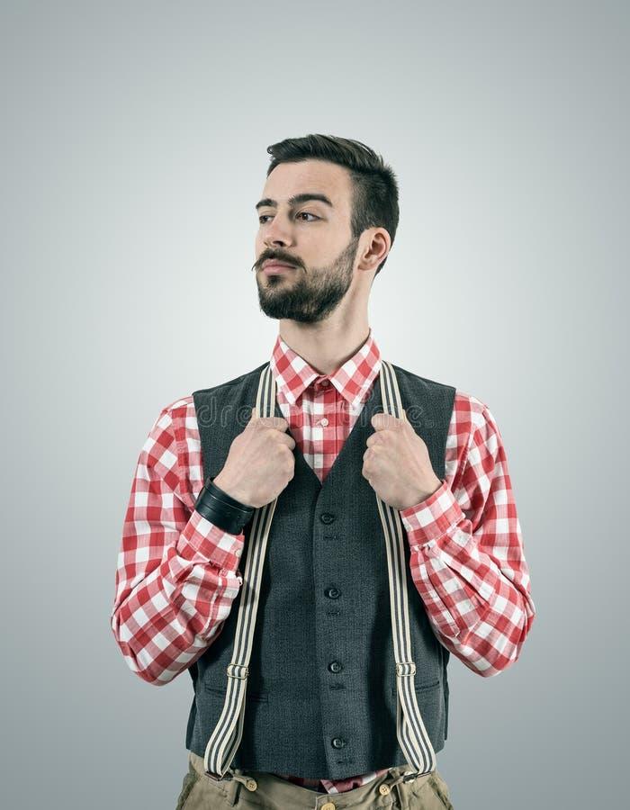 Modèle de hippie regardant loin avec le sourcil augmenté tout en tenant ses bretelles de pantalon image libre de droits