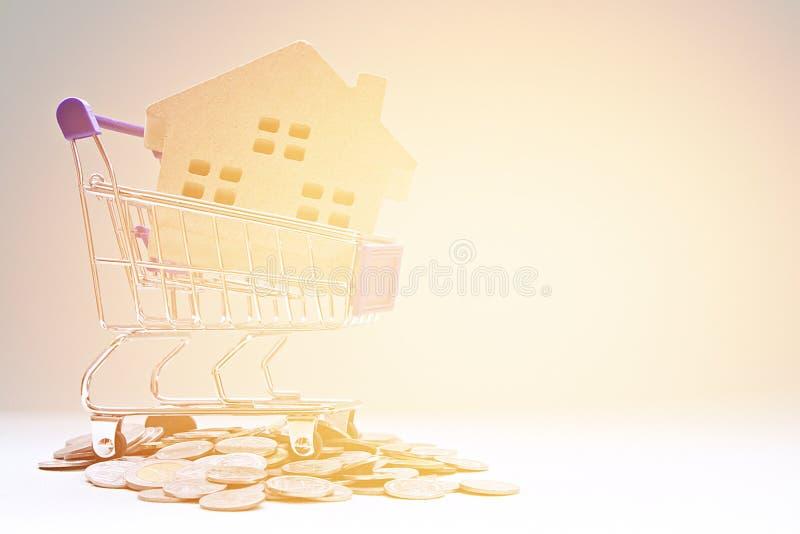 Modèle de maison en bois, pièces de monnaie et caddie sur la table de bureau images libres de droits