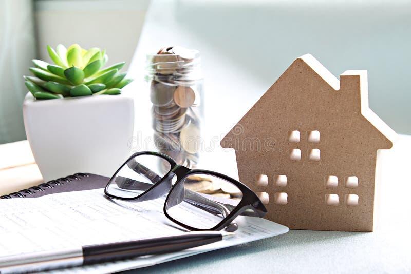 Modèle de maison en bois, pièces de monnaie, lunettes et livre de comptes d'économie ou relevé de compte financier sur la table d image libre de droits