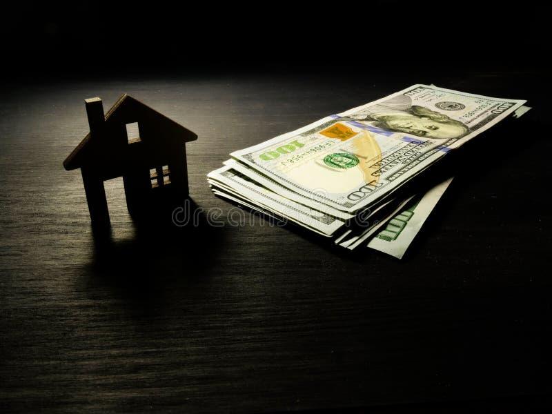 Modèle de maison et d'argent dans l'obscurité Hypothèque ou dollars pour le loyer image stock
