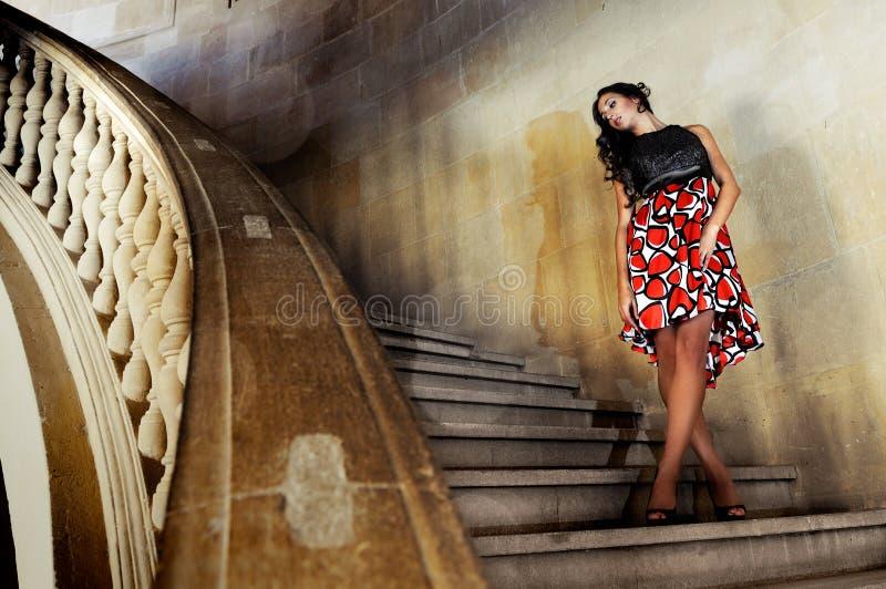 Modèle de mode avec la robe de créateur sur des escaliers image stock