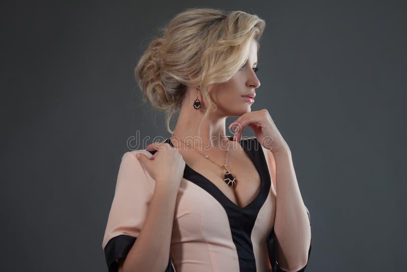 Modèle de mode avec le cheveu blond Jeune femme attirante, fond élégant et gris photos stock