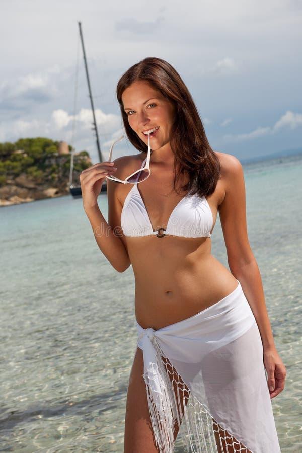 Modèle de mode de cheveu de Brown dans le bikini par la mer images libres de droits